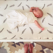 crib sheet with baby arms out asleep