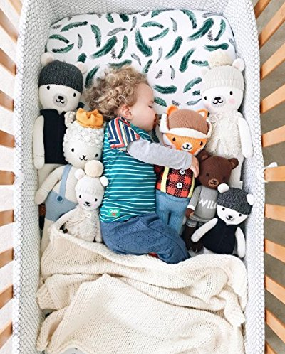 green feather crib sheet with toys