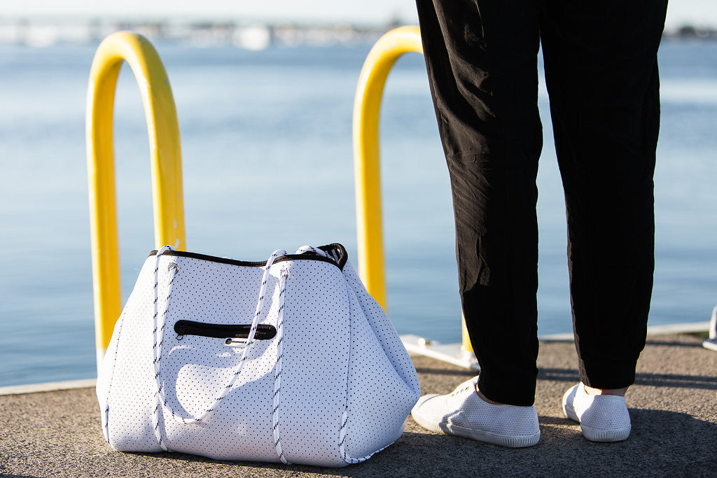 white diaper tote bag by water