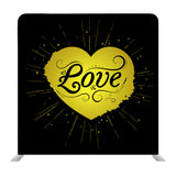 Gold foil heart sticker on black background Backdrop