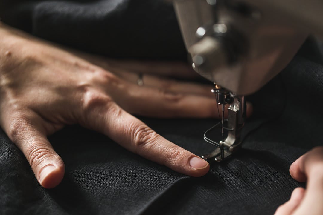 Using a sewing machine to stitch charcoal gray wool fabric