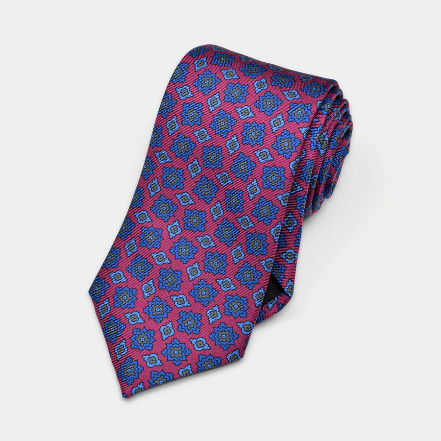 Rolled magenta foulard tie with blue and grey accents