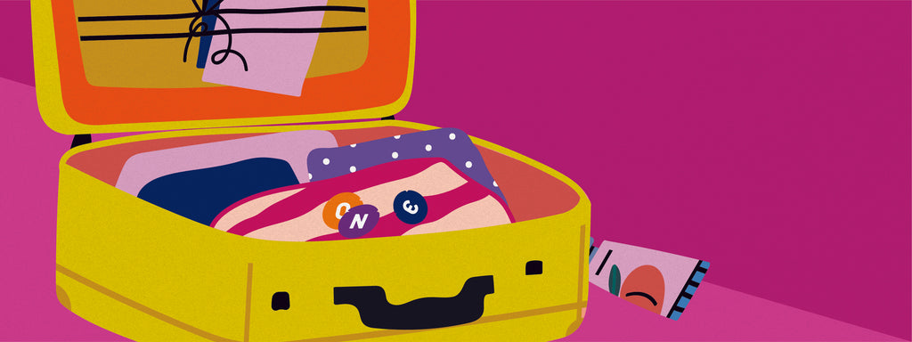 A suitcase packed with clothes with three ONE Condoms on top.
