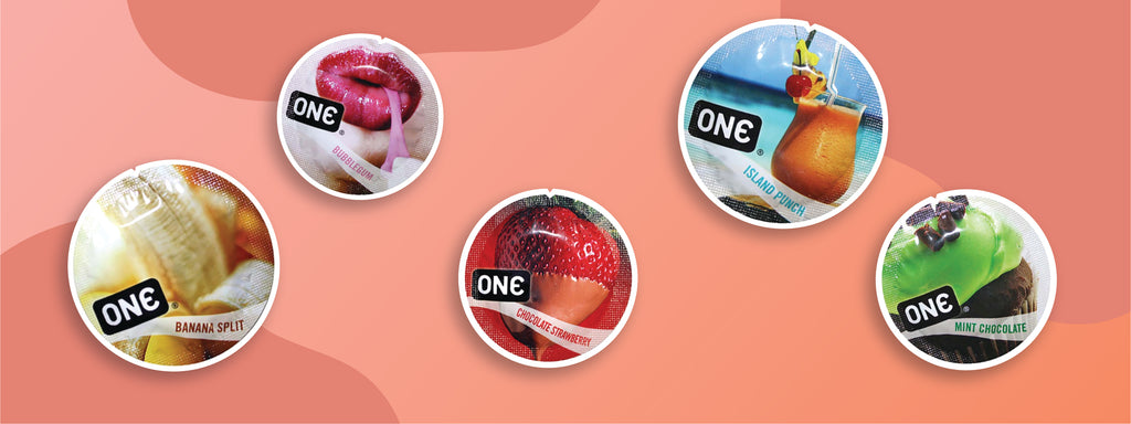 Five ONE Condom wrappers each with fruit on them. Flavorwaves condoms are flavored condoms that can be used for oral or penetrative sex. Flavors shown are banana split, bubblegum, chocolate strawberry, island punch, and mint chocolate.