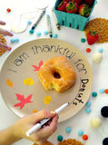 Girl writing I am thankful for donuts on tan fall themed plate
