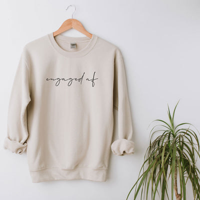 "Custom Bride-to-Be Engagement or Bachelorette Sweatshirt with ""engaged af"" in lowercase script across chest."