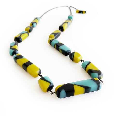 A beautiful multicoloured long necklace made from lime green and teal off-cuts cast in black resin. Strung on double chains oxidised silver chain, finished with a matching resin clasp.  Entirely handmade in Brighton.