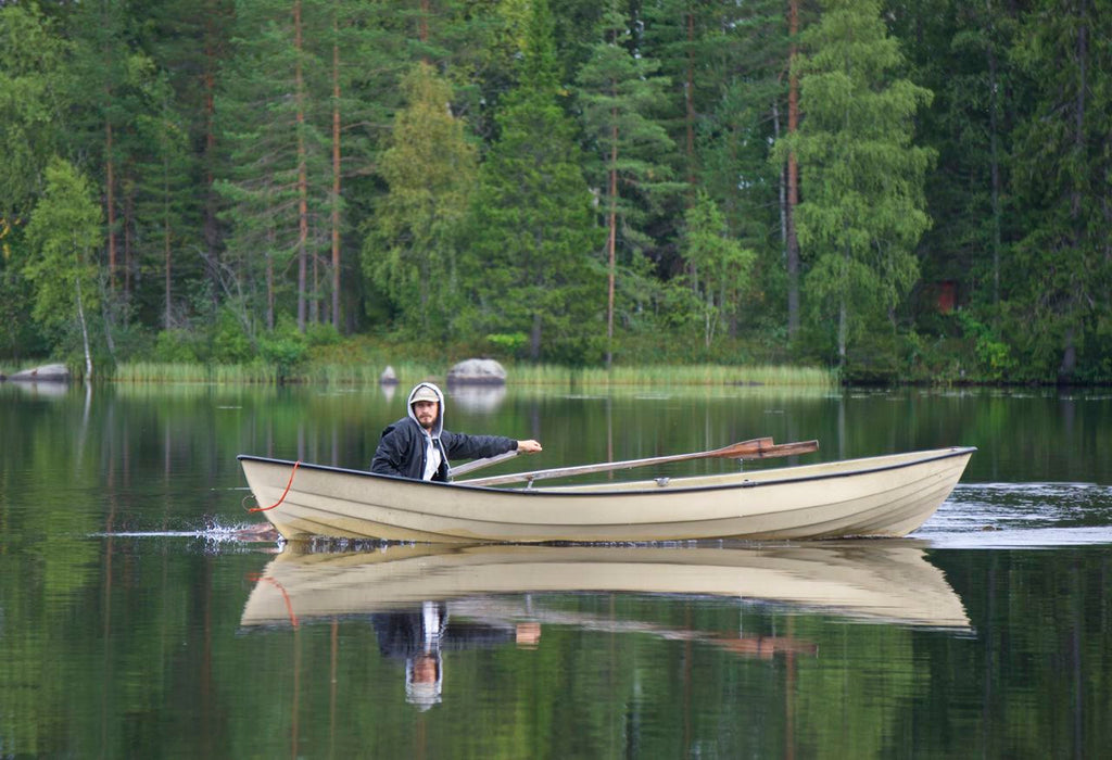 picture of Finnish lake in the summer: a Finnish man rowing a boat
