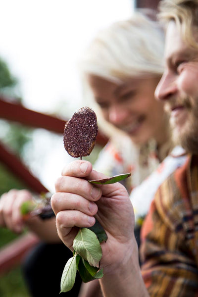 Picture of Annika Hannus and Nick Victorzon eating Chokeberry Birch Sugar Lollypop from the book Villiyrtit – hyvinvointia kotikulmilta (WSOY)