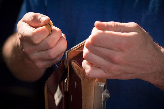 An employee hand stitches a new leather wallet.