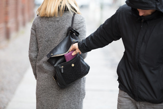 Pickpocket taking wallet from woman's purse