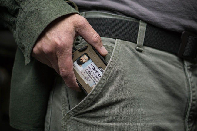 Trayvax Axis bi-fold wallet in FDE being placed into pocket