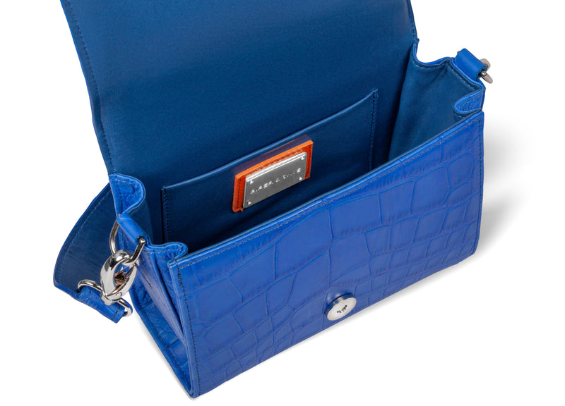 inner view of luxury handbag in cobalt leather with crossbody strap