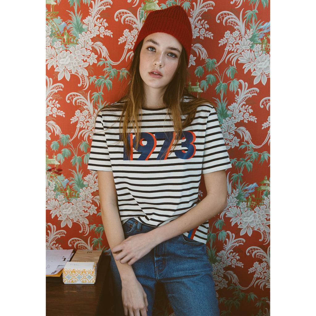 The Modern 1973 - White/Royal/Poppy on Model with Hat, Jeans and Red Floral Wallpaper