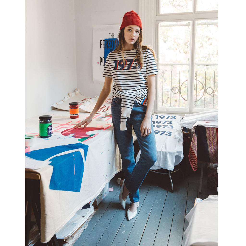 The Modern 1973 - White/Royal/Poppy on Model with Red Hat, Jeans in Print Shop