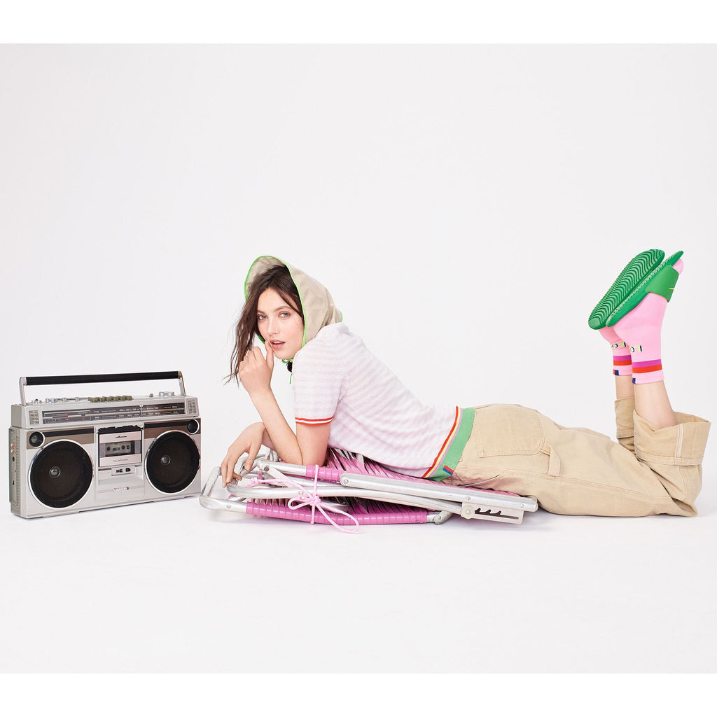 The Corinne - Pink/White on model on chair with boombox laying down