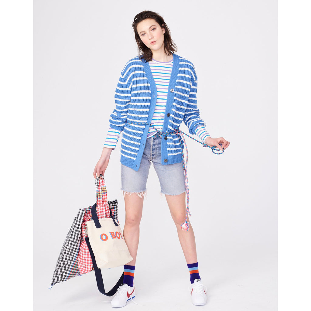 The O S#!T Sock - Purple on Model with Blue Sweater, Blue Stripe Shirt and Jean Shorts