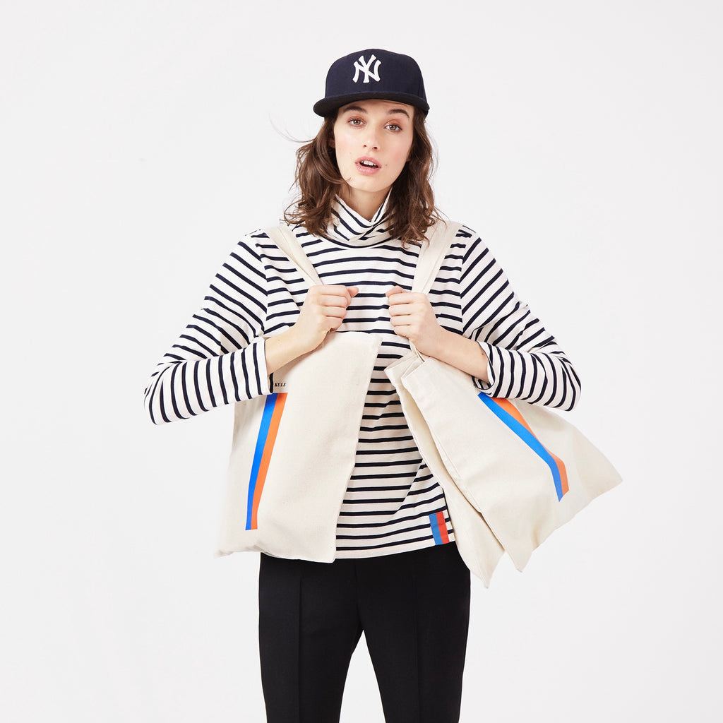 The Turtleneck in Cream/Navy on Model with Black Pants and KULE bags