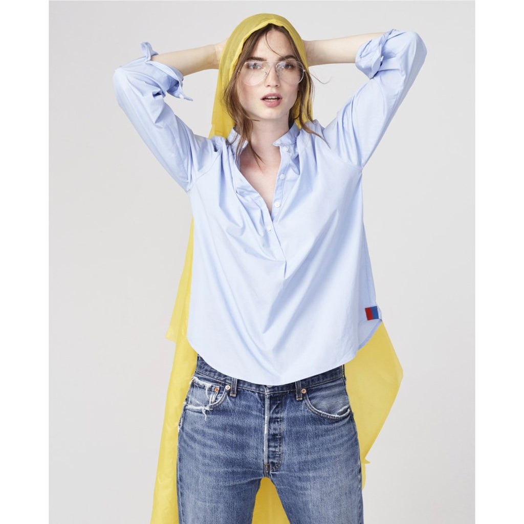 The Brooke - Blue on model with jeans and yellow rain coat with hands up