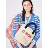 The O BOY Bucket Flat, Canvas crossbody with o boy writing in poppy with blue shadow on model