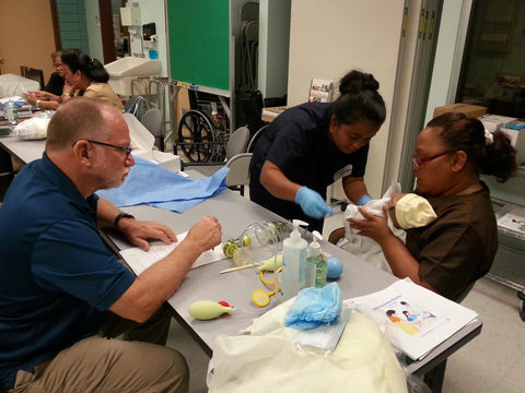 Dr. James Finch, a nursing instructor at the University of Guam, looks on as Jessica Kerman, an emergency room nurse from Pohnpei State Hospital, performs a procedure during a training session on helping newborns to breathe.