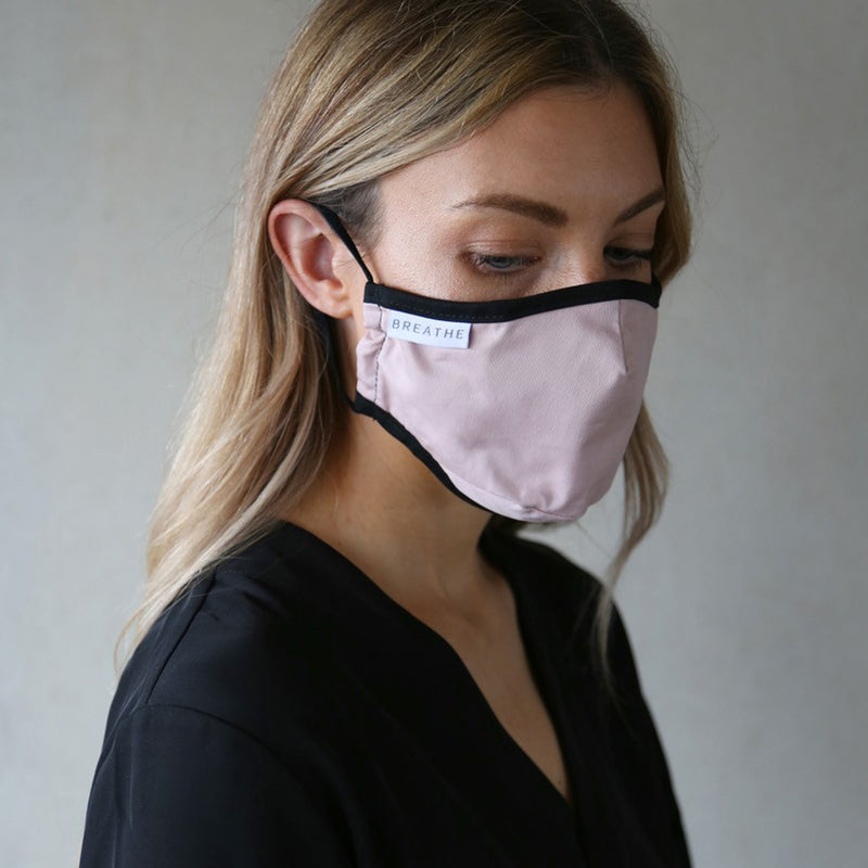 Woman wears an organic cotton face mask by BREATHE in pink