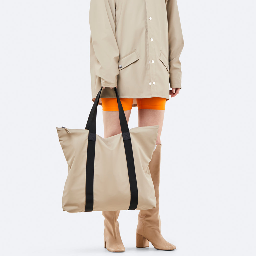 Woman Holding Rains Tote Rush in Beige, available at ALC Edinburgh
