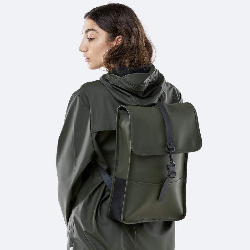 Woman wearing the Backpack Mini in Green by Rains