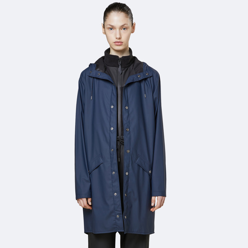 Woman wearing long blue waterproof jacket by Rains