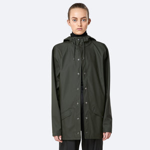 Woman wears the green short waterproof jacket by Rains