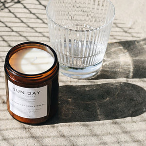 Lifestyle image of a Sun.Day candle. This page is for the Midnight scent