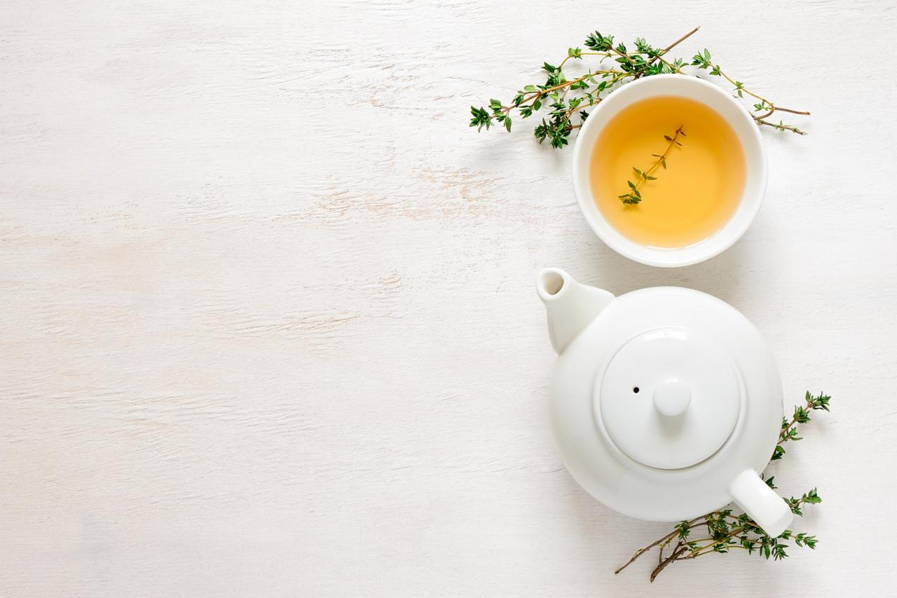A cup of herbal tea, a teapot and some fresh rosemary
