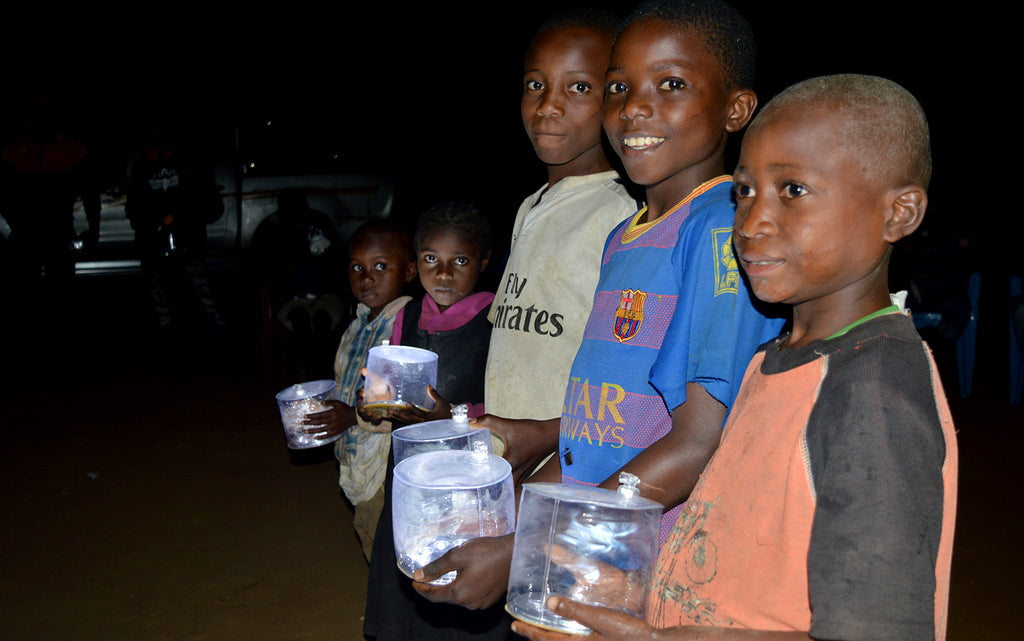 Olf hands out lights in his hometown, Mbaya, Congo