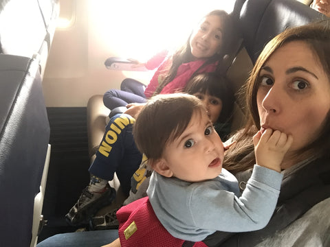[Caption: Four kids on a plane—and look! No one's crying! Photo credit: Lisette Haddad.