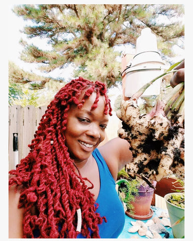 Adiva Naturals Founder Nadira Chase hold up fresh Ginger from her garden