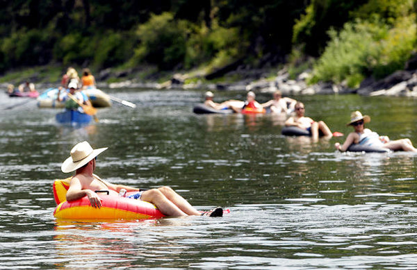 a group of people float in inner tubes down a glassy, slow flowing Clark Fork River near Missoula.