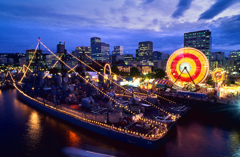 A view of the Portland Rose Festival with a ferris wheel and bustling pier.