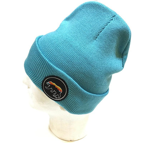 An aqua blue beanie hat, with  a sunset colored griz on the side.