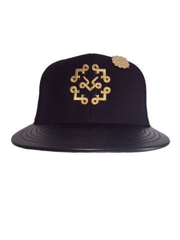Black & metallic gold Lotta Pieces snap back, black leather bib and gold pin.
