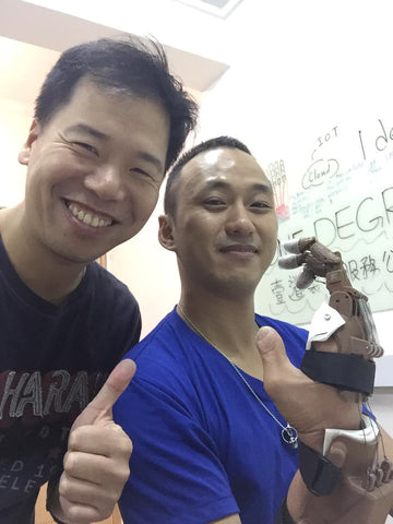 Mike Li (left) and Eric (right) displaying the fully installed prosthetic hand.