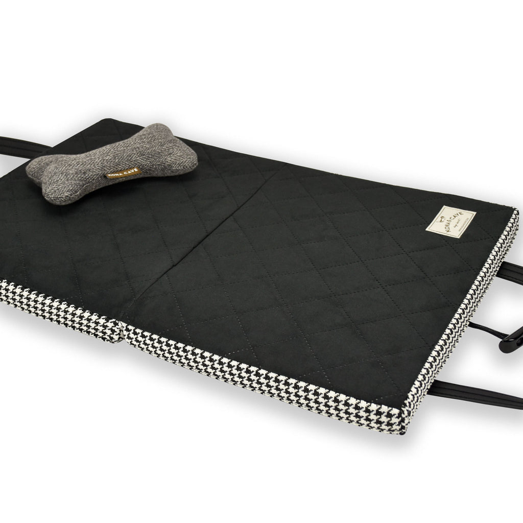 Open KONA CAVE® Travel Dog Bed in Black and White Houndstooth with Black Quilted Ultra-Suede Lining with a Toy Dog Bone on top