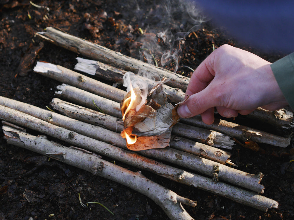 Laying more birch bark to create a bigger fire.
