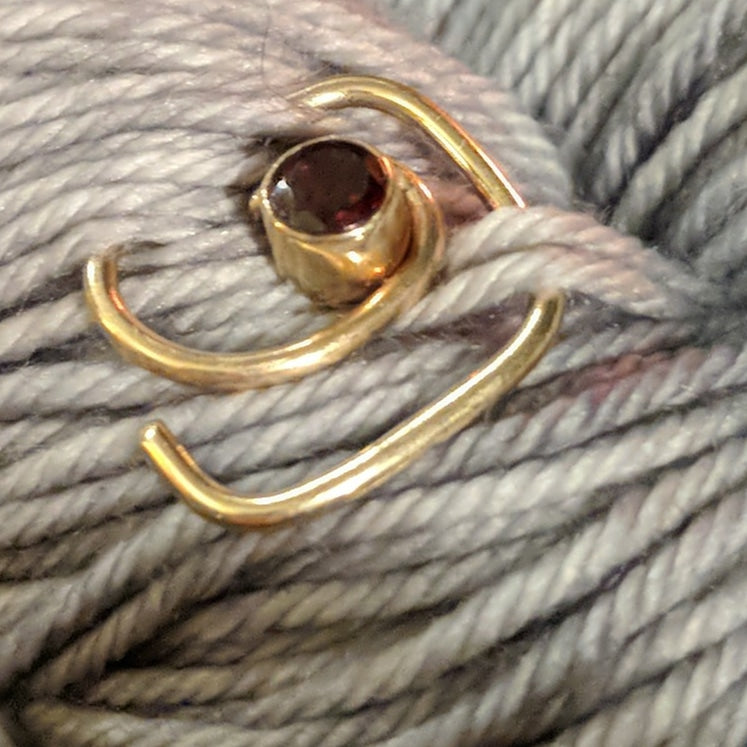 Gold twisty-in-pin, set with a garnet.