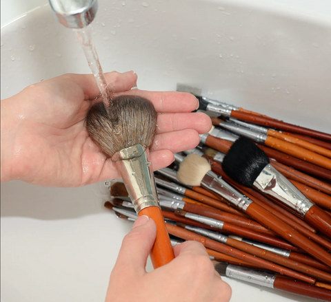 A set of hands washing some makeup brushes in a sink with running water