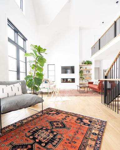 vintage rug in living room with armchair and high ceilings