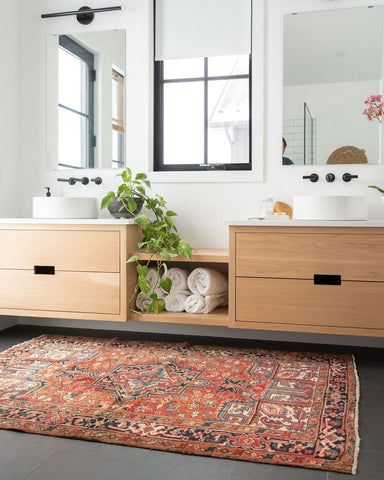 stunning red and blue vintage rug in front of his and hers sink in a neutral bathroom