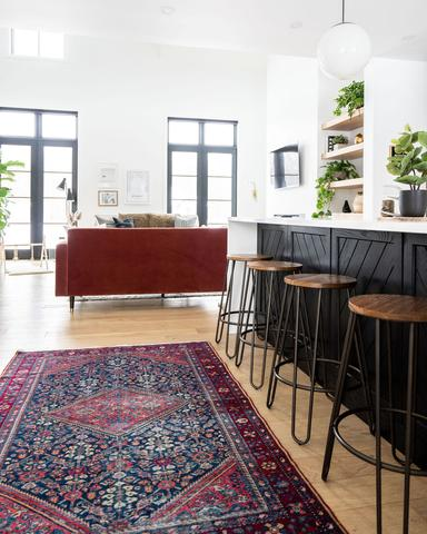 shot of bar stools and vintage rug with black centre island