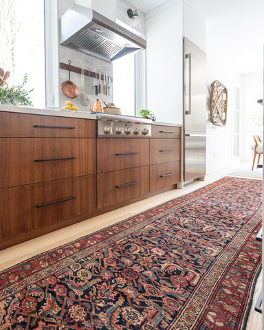 vintage Persian runner that is red and blue alongside a modern kitchen with stainless steel appliances and wood finishings