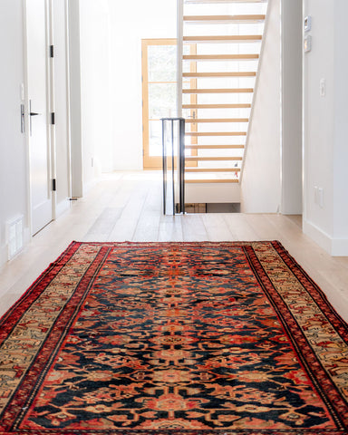 beautiful vintage Persian area rug in open concept hallway leading to see through stair case in a modern home