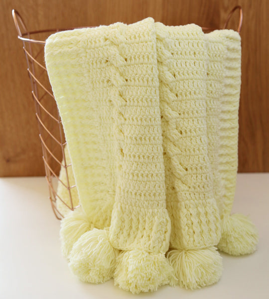 Crochet blanket with pom pom in yellow